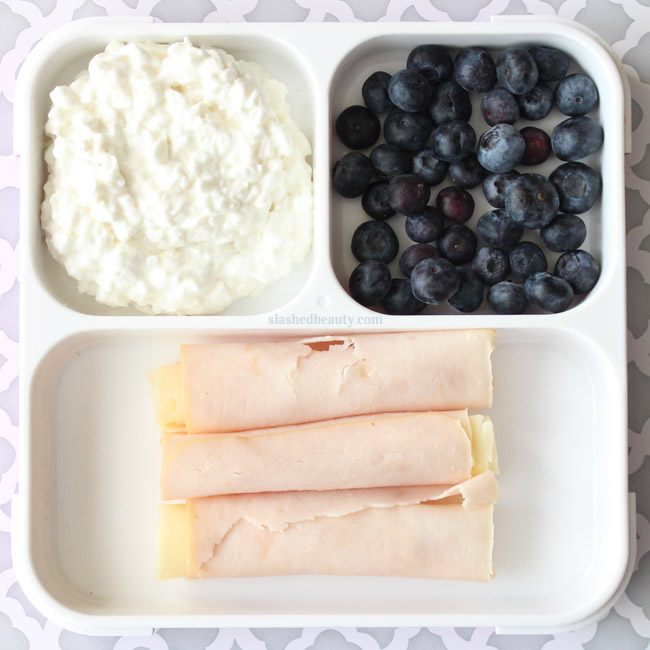 Need some healthy snack inspiration for work or school? Here are three snack pack ideas that will keep you full and on track with your fitness goals! Cottage Cheese, Blueberries & Turkey Swiss Roll Ups | Slashed Beauty